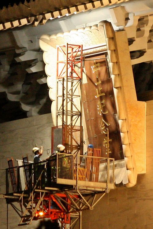 Workers install the plaque 'Chiang Kai-shek Memorial Hall' yesterday evening.