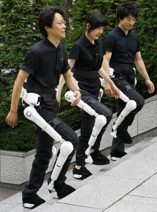 Cyberdyne Inc. employees, from left, Masatoshi Kameoka, Fumi Takeuchi and Takatoshi Kuno, all wearing the Japanese company's robot suits HAL walk on s...