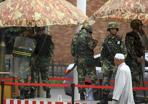 An ethnic minority Chinese resident walks past a checkpoint with heavily armed paramilitary police along a street of Urumqi, northwestern China's Xinj...