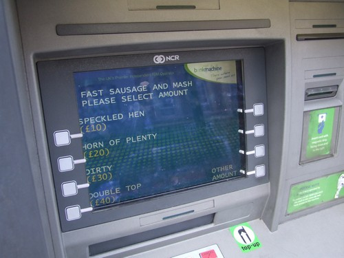 The screen of an ATM cash machine in East End neighborhood of Whitechapel, London, England, offers two language options of English or Cockney as it is...