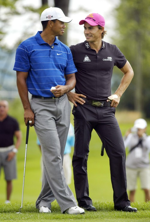 Tiger Woods, left, and Camilo Villegas chat while waiting to putt on the 15th green during the Notah Begay III Foundation Challenge at Atunyote Golf C...