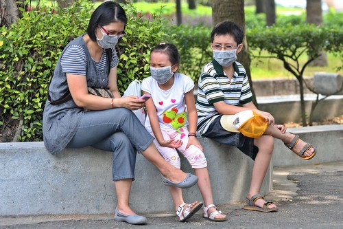 A woman and two children wearing surgical masks take a rest in a park in Taipei yesterday.