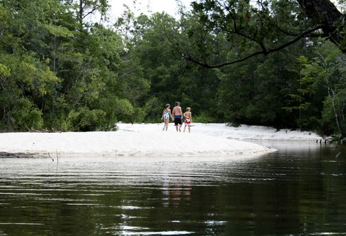 A family walks the sandy shore at Blackwater River State Park, one of the many state parks near Destin, Florida on July 24.