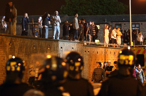 British police officers in riot gear surround soccer supporters outside Upton Park stadium, London, England on Tuesday.