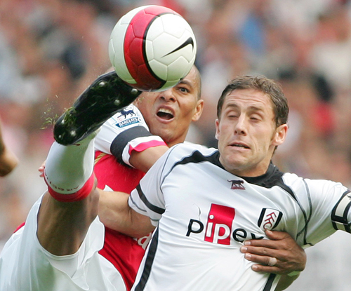 Arsenal's Julio Baptista, left, scores a goal above Fulham's Philippe Christanval, right, and Liam Rosenior (C) during their English Premier League ma...