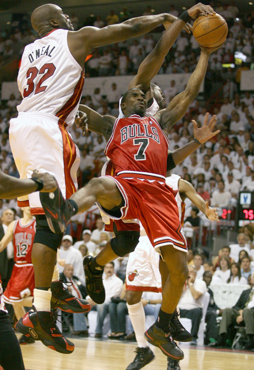 Chicago Bulls Ben Gordon, right, is fouled by the Miami Heat's Shaquille O'Neal in Game 4 of their Eastern Conference NBA basketball playoff in Miami,...