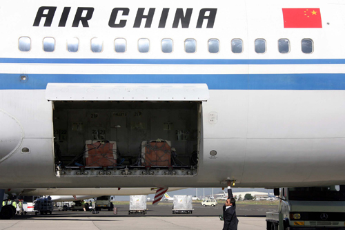 In this photo released by China's Xinhua News Agency, a crew member closes the cabin containing the coffins of 9 Chinese victims of an attack by Ethio...