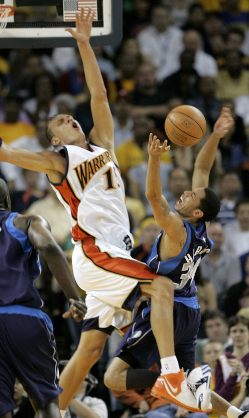 Dallas Mavericks Devin Harris, right, and Golden State Warriors Andris Biedrins collide while chasing a rebound during Game 4 of their NBA Western Con...