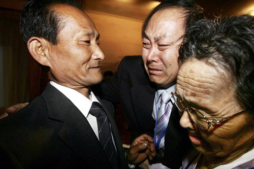 An 88-year-old South Korean woman, right, meets her 62-year-old North Korean son, left, as his South Korean brother, center, cries during a family reu...