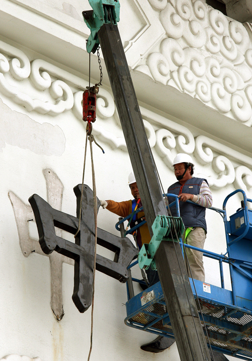"""Workers remove the character """"zhong"""" from the """"da zhong zhi zheng"""" inscription on the main gateway of the Taiwan Democracy Memorial Hall yesterday aft"""