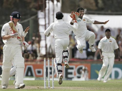 Sri Lankan bowler Mauttaiah Muralitharan, jumping right, celebrates the dismissal of England's batsman Paul Collingwood, left, during the last day of ...