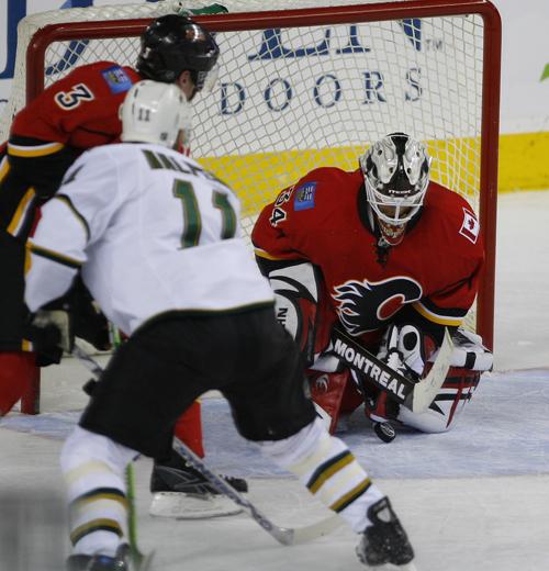 Calgary Flames goalie Miikka Kiprusoff, right, stops a shot by Dallas Stars Jeff Halpern, left, as Calgary's Dion Phaneuf looks on during the third pe...