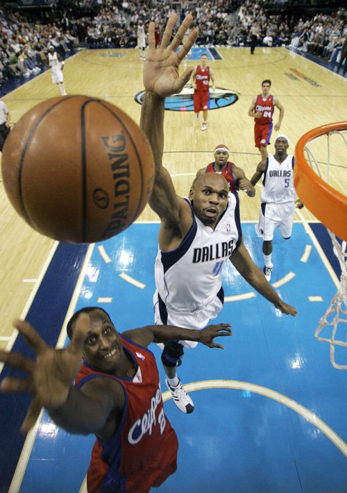 Los Angeles Clippers guard Brevin Knight, bottom, drives to the basket under pressure from Dallas Mavericks forward Jerry Stackhouse in the first half...