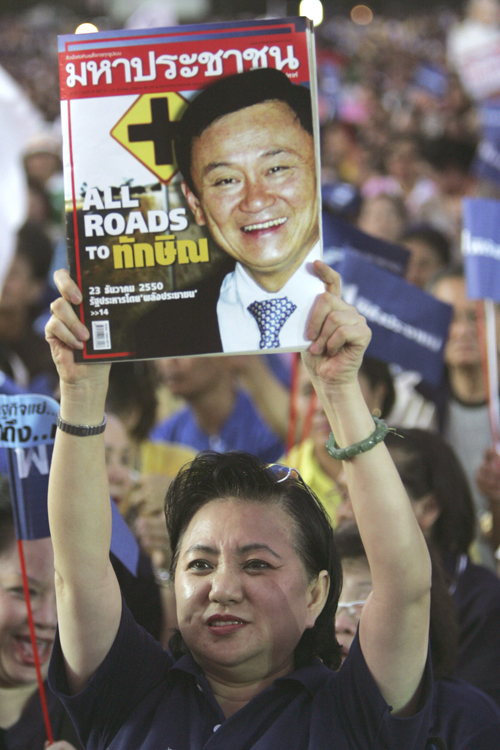 A supporter of People's Power Party holds a copy of a weekly magazine showing the image of former Thai Prime Minister Thaksin Shinawatra during the pa...