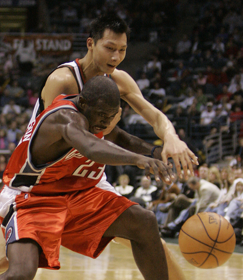 The Milwaukee Bucks' Yi Jianlian, of China, and the Charlotte Bobcats' Jason Richardson (23) stretch for a loose ball during the second half of an NBA...