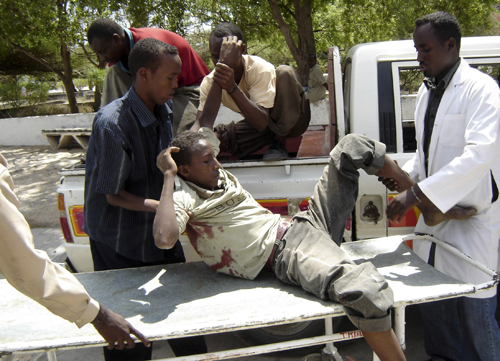Health workers assist resident wounded in fighting in Mogadishu, Somalia on Saturday.