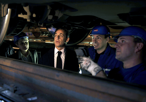 French President Nicolas Sarkozy, center, listens to explanations during a surprise visit in a maintenance site of the national rail operator SNCF, in...