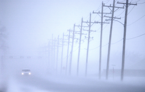 A car travels on Schilling Road in blizzard conditions on Saturday in Salina, Kansas.