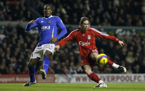 Liverpool's Fernando Torres, right, scores against Portsmouth despite the attention of Sylvain Distin during their English Premier League match in Liv...