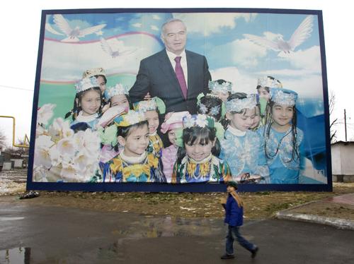 A boy walks past an electoral poster of Uzbekistan's President Islam Karimov in Tashkent, Uzbekistan yesterday.