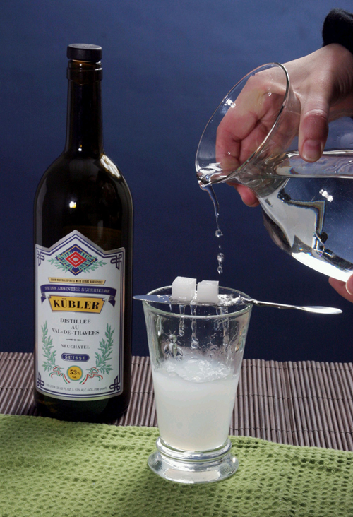 Water is drizzled over sugar cubes into a glass of absinthe liquor.