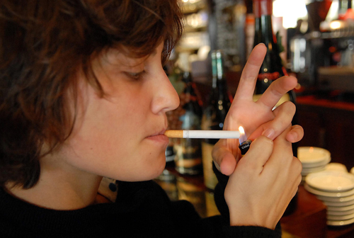 In this file photo, a woman is seen lighting a cigarette in a cafe in Paris, France. French Prime Minister Dominique de Villepin pledged to ban smokin...