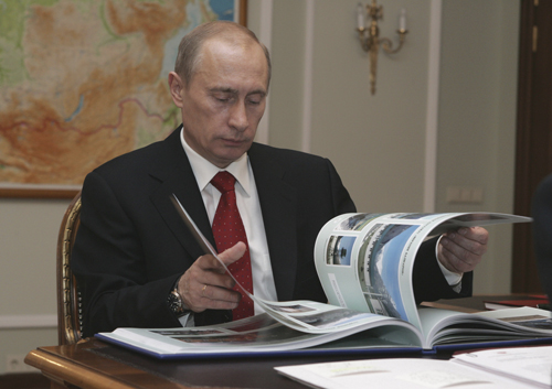 Russian President Vladimir Putin looks through a book during a meeting with Nikolai Patrushev, unseen, the head of Federal Security Service at his stu...
