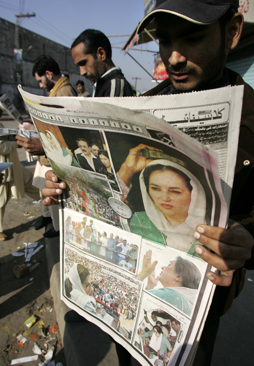 People read the morning newspapers with headline stories of Pakistan's  former Prime Minister Benazir Bhutto's assassination, at a newspaper stand in...