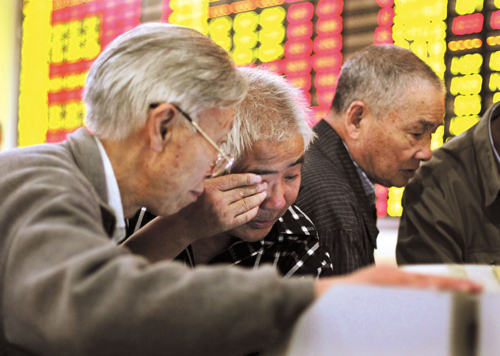 Stock investors monitor the stock prices at a securities company in Shanghai, China in this file photo. Investors in China poured their money into sha...