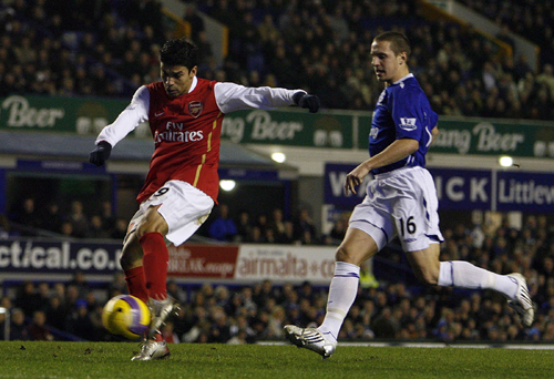 Arsenal's Eduardo, left, scores as Everton's Phil Jagielka watches during their English Premier League soccer match at Goodison Park in Liverpool, nor...