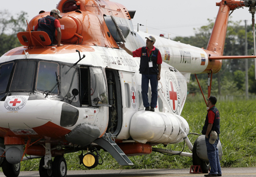 The crew of a MI-17 helicopter with Red Cross insignia prepare it at an airport in Villavicencio, Colombia on Saturday. Venezuelan rescue teams waited...