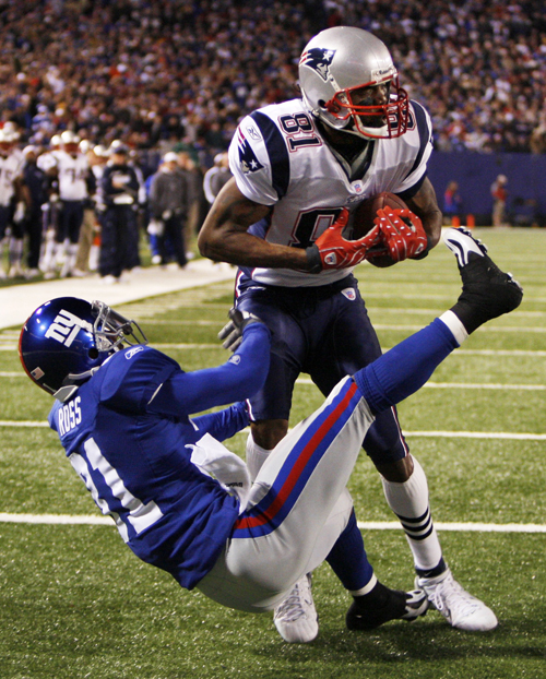 New England Patriots wide receiver Randy Moss scores on a 4-yard touchdown pass from quarterback Tom Brady against New York Giants cornerback Aaron Ro...