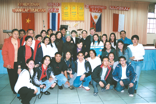 Filipino volunteers at the Hope Workers' Center in Jhongli City join Bishop John Baptist Lee, center and wearing a Roman collar, and the Reverend Pete...