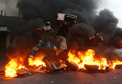 Lebanese protesters hold banners and jump through burning blockades in the southern city of Sidon, Lebanon on Tuesday.