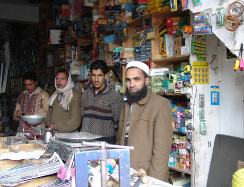 Anwal Faroze, far right, stands behind the counter at his hardware shop in the bazaar in Allai Valley.