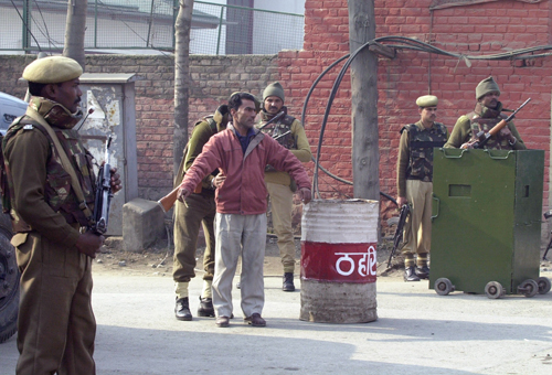 Indian police officers belonging to the Central Reserve Police Force frisk a Kashmiri man near a check point during a search operation in Srinagar, In...