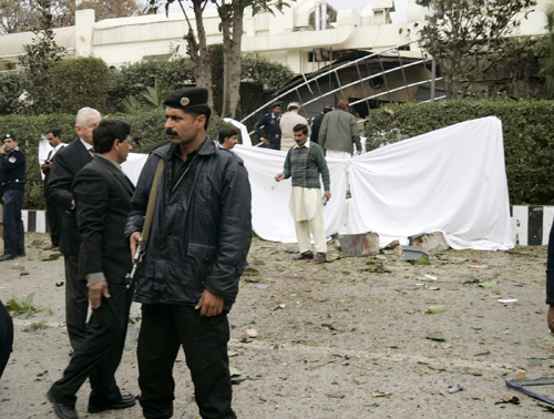 Pakistani police examine the site of an bomb explosion, outside the Marriott Hotel in Islamabad yesterday.