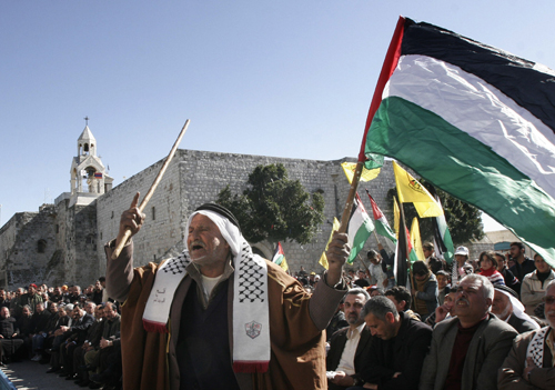 A man holds a Palestinian flag during a rally marking the 42nd anniversary of the Fatah Movement next to the Church of the Nativity in the West Bank t...