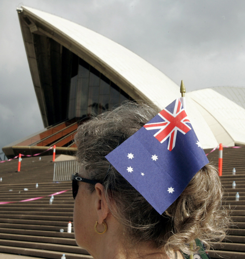 A woman wears an Australian flag in her hair as she walks past the Sydney Opera House during Australia Day celebrations in Sydney yesterday.