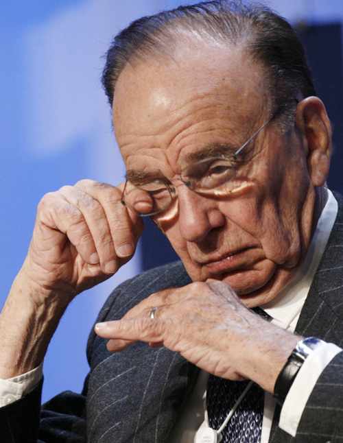 "Media tycoon Rupert Murdoch, CEO of News Corporation, wipes his eye during the session ""Who Will Shape the Agenda?"" yesterday."