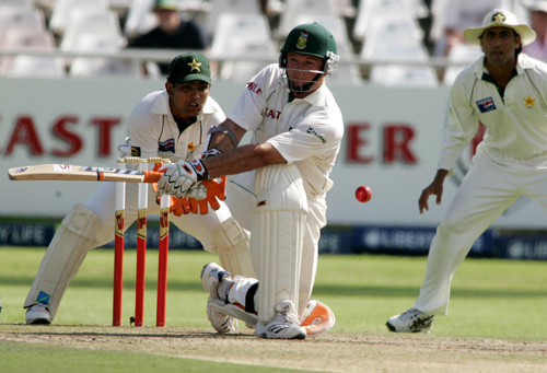 South African captain Graeme Smith, center, plays a stroke as Pakistan's wicket keeper Kamran Akmal, left, anticipates a catch on the first day of a t...