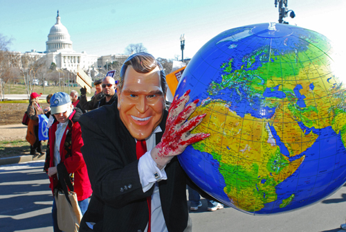 A man wearing a mask of U.S. President George W. Bush carries a globe during the anit-war protest on the National Mall in Washington, D.C. on Saturday...