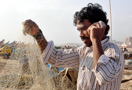 A fisherman speaks on his mobile phone on the outskirts of Chennai, India earlier this month. In millions of ways worldwide, cell phones are making it...