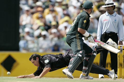 Australia's Matthew Hayden, center, turns to see New Zealand's Ross Taylor dive to field the ball as umpire Ranjan Madugalle watches in their one day ...
