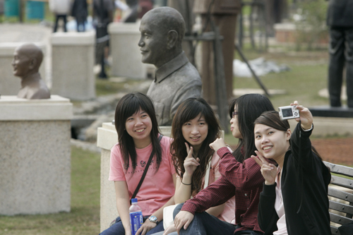 Young tourists pose for a photograph with statues of the late Kuomintang leader Chiang Kai-shek at a mountainside park on February 13 in Tashi, northe