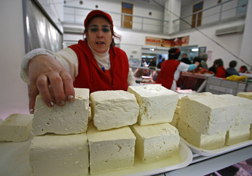 A woman arranges a piece of traditional Romanian cheese at Obor market in Bucharest on February 9.