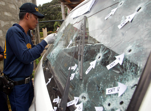 A police officer inspects bullet holes in a vehicle after a gun battle between feuding politicians in the rice-growing town of Jaen in Nueva Ecija pro...