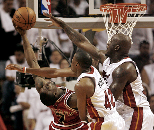 The Chicago Bulls' Ben Gordon, left, is fouled as the Miami Heat's James Posey, center, and Shaquille O'Neal defend during Game 3 of their NBA playoff...