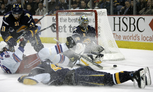 Buffalo Sabres goalie Ryan Miller, background center, makes a save as the New York Rangers' Jaromir Jagr (68) is tripped by the Sabres' Dmitri Kalinin...