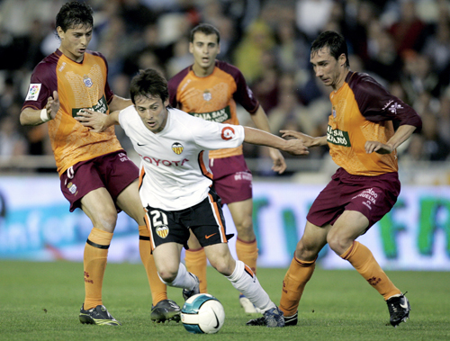 Valencia's David Silva from Spain, second left, duels for the ball with Recreativo Huelva players Jesus Vazquez from Spain, left, Juanma Gomez from Sp...